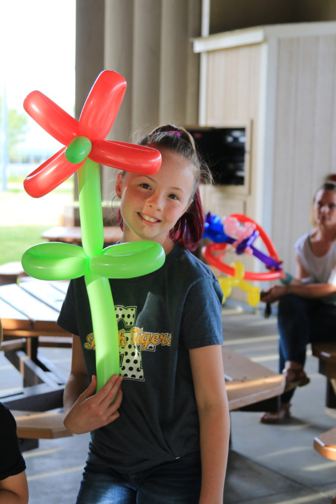 BQMI Team Picnic 15 June 2018 participant with a balloon flower made by Magic Mike.